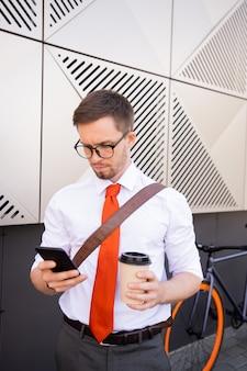 Junger ernsthafter geschäftsmann, der im smartphone rollt und kaffee trinkt, während er am morgen entlang der wand des geschäftszentrums ins büro geht