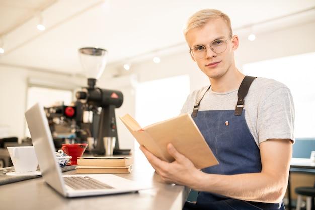 Junger ernsthafter gutaussehender mann in brillen und arbeitskleidung von barista, der sie beim lesen der literatur über restaurantgeschäft ansieht