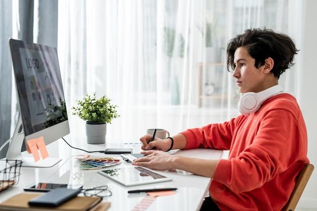 Junger ernsthafter männlicher designer, der computerbildschirm beim sitzen am schreibtisch betrachtet und foto oder logo retuschiert