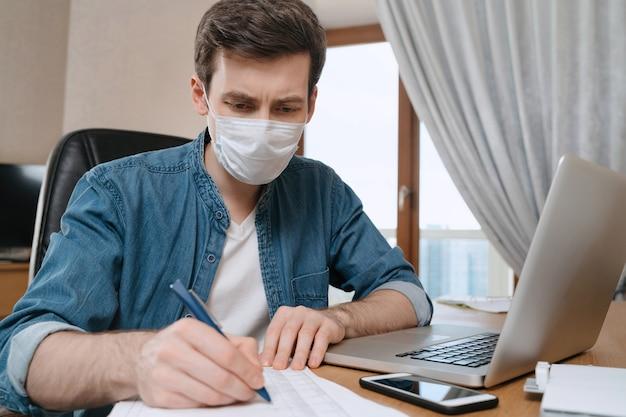 Junger ernsthafter mann in der medizinischen gesichtsmaske, die aufgrund des coronavirus- oder covid-19-ausbruchs ferngesteuert mit laptop studiert.