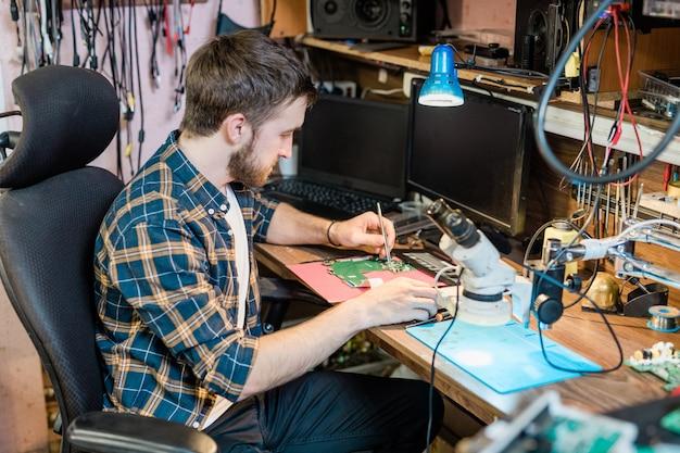 Junger ernsthafter mechaniker oder handwerker mit kleinem stahlhandwerkzeug, das demontiertes touchpad oder anderes gerät repariert