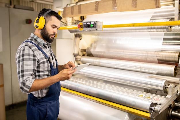 Junger ernsthafter qualitätskontrollingenieur, der tablette verwendet, um parameter des verarbeiteten materials zu überprüfen, während er zur produktionsmaschine steht