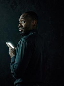 Junger ernsthafter schwarzafrikaner, der denkt, während auf handy gegen schwarzen studiohintergrund spricht