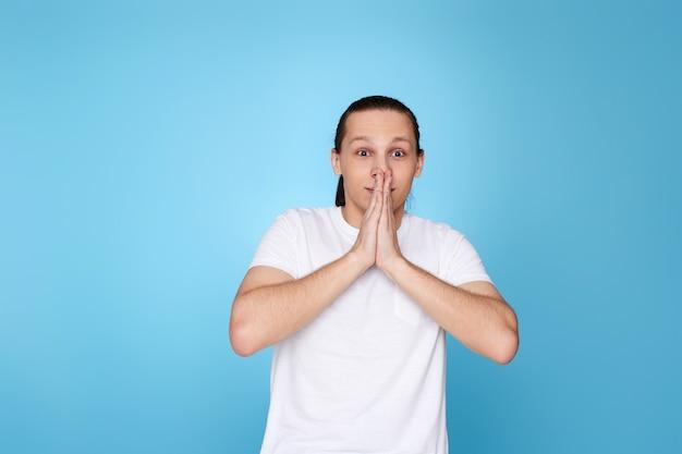 Junger erschrockener mann im t-shirt lokalisiert auf blauem hintergrund.