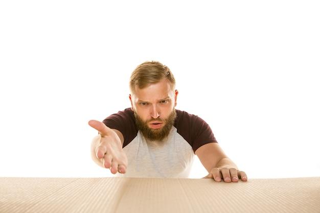 Junger erstaunter mann, der das größte postpaket lokalisiert auf weiß öffnet. schockiertes männliches model oben auf dem karton, der nach innen schaut.