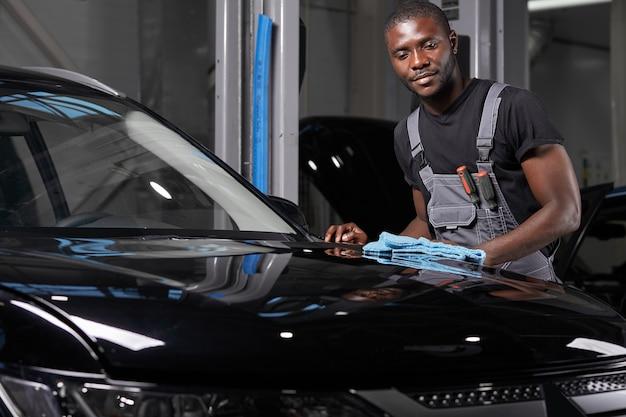 Junger erwachsener afroamerikanischer mann, der auto mit mikrofasertuch reinigt