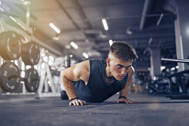 Junger erwachsener athlet, der liegestütze als teil des bodybuilding-trainings tut.