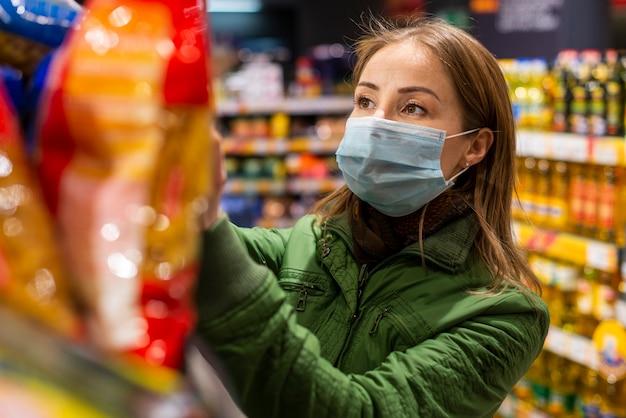 Junger erwachsener, der eine schutzmaske trägt und produkte kauft