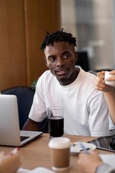 Junger erwachsener, der in einem café studiert