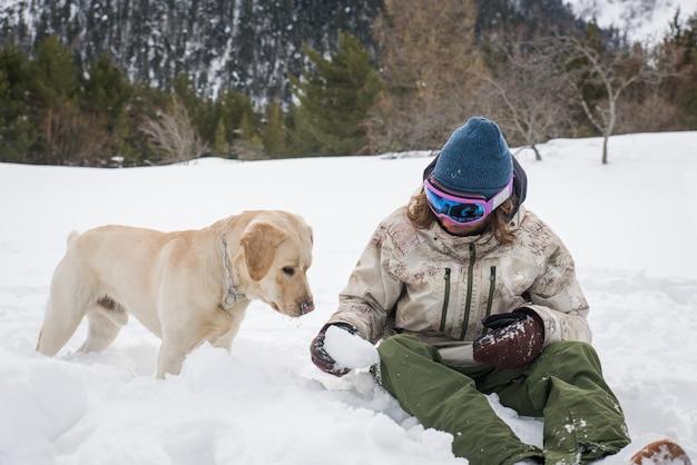 Junger erwachsener, der mit seinem hund spielt