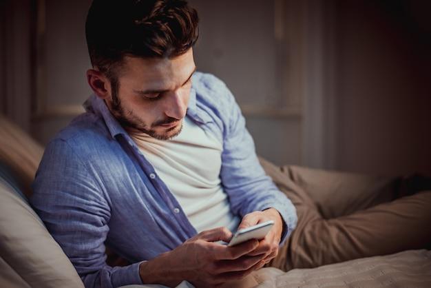 Junger erwachsener, der smartphone zu hause benutzt