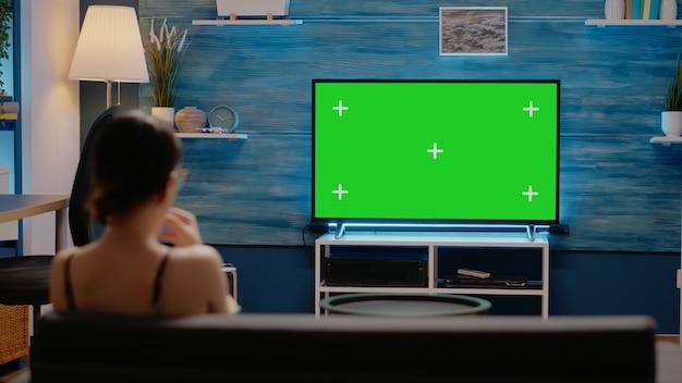 Junger erwachsener, der zu hause greenscreen im fernsehen sieht