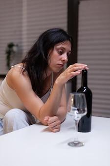 Junger erwachsener, der zu hause wein allein in der küche trinkt