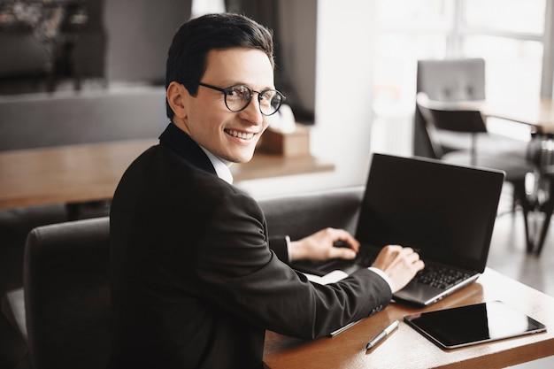 Junger erwachsener freiberufler mit brille, die kamera über der schulter lächelnd beim arbeiten an seinem laptop in einem café betrachtet.