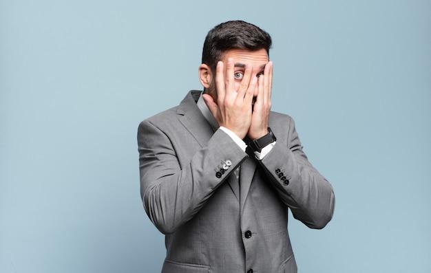 Junger erwachsener gutaussehender geschäftsmann, der das gesicht mit den händen bedeckt, zwischen den fingern mit überraschtem ausdruck späht und zur seite schaut