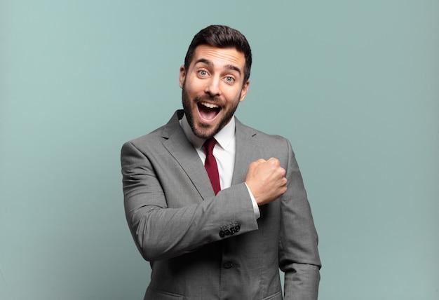 Junger erwachsener, gutaussehender geschäftsmann, der sich glücklich, positiv und erfolgreich fühlt, motiviert, wenn er sich einer herausforderung stellt oder gute ergebnisse feiert