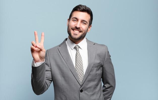 Junger erwachsener hübscher geschäftsmann, der lächelt und glücklich, sorglos und positiv schaut, sieg oder frieden mit einer hand gestikulierend
