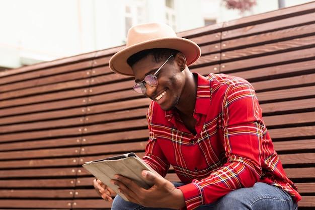 Junger erwachsener im roten hemd, das auf einer bank sitzt