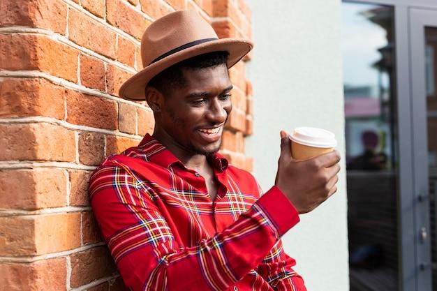 Junger erwachsener im roten hemd, das die tasse kaffee betrachtet