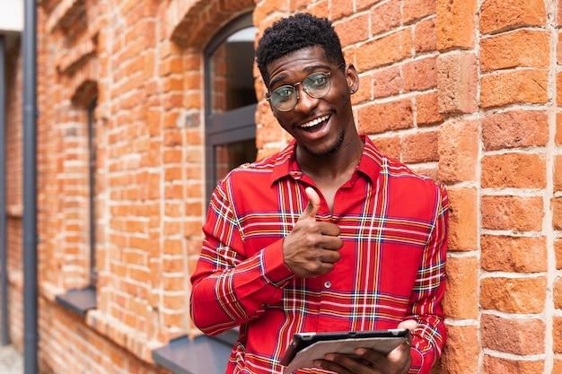 Junger erwachsener im roten hemd, das ein niedliches lächeln hat