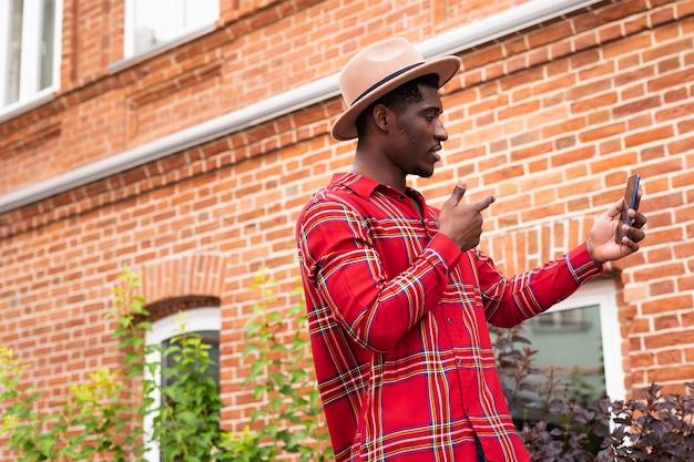 Junger erwachsener im roten hemd, das ein selbstfoto neben einem backsteinmauerngebäude macht