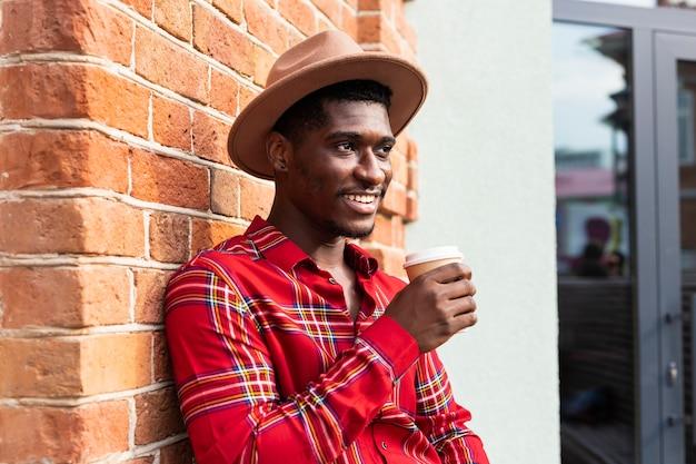 Junger erwachsener im roten hemd, das eine tasse kaffee hält