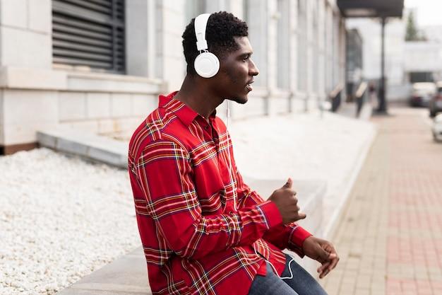 Junger erwachsener im roten hemd, das musikseitenansicht hört