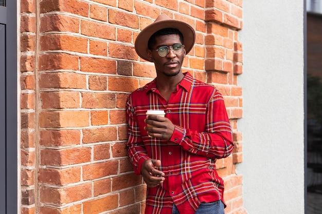 Junger erwachsener im roten hemd, das wirklich zuversichtlich aufwirft