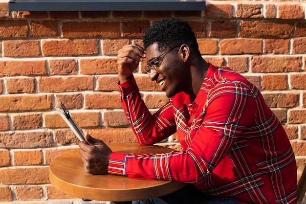 Junger erwachsener in der seitenansicht des roten hemdes
