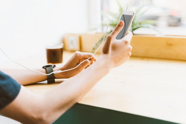 Junger erwachsener junge, mann, textnachricht der nicht erkennbaren person auf smartphone und hören musik