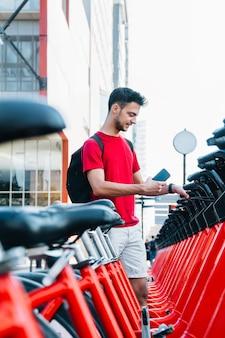 Junger erwachsener kaukasischer student, der mit seinem smartphone ein fahrrad mietet