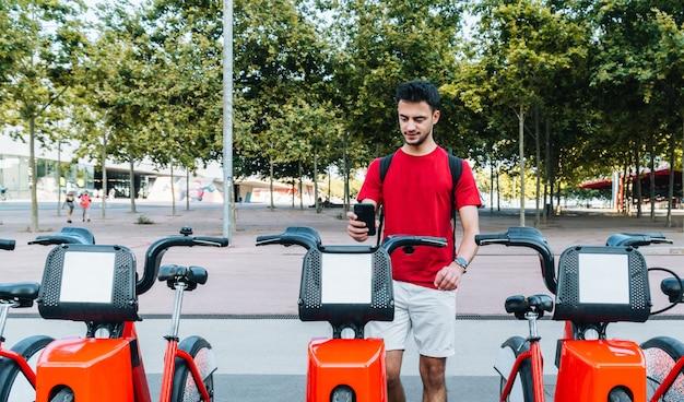 Junger erwachsener kaukasischer student, der mit seinem smartphone ein leihfahrrad bucht