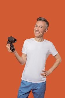 Junger erwachsener lächelnder mann, der mit fernglas steht