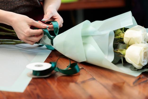 Junger erwachsener mädchenflorist macht einen blumenstrauß von weißen rosen. nahaufnahmefoto.