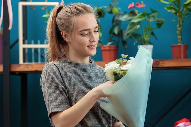 Junger erwachsener mädchenflorist macht einen blumenstrauß von weißen rosen.