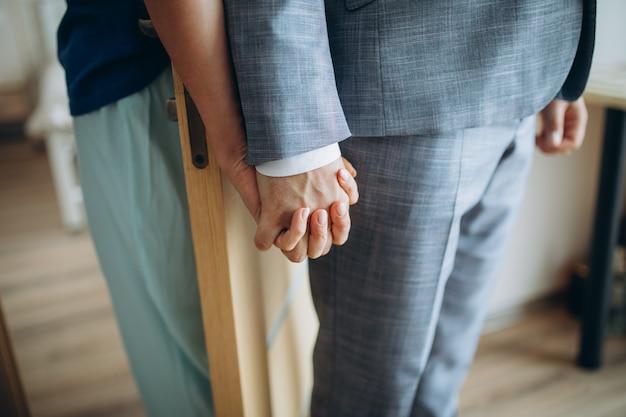 Junger erwachsener männlicher bräutigam und weibliche braut, die hände halten