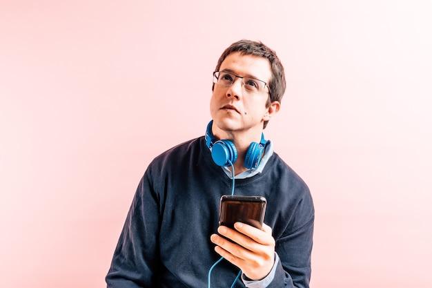 Junger erwachsener mann fünfunddreißig jahre alt in hemd und blauem pullover mit v-ausschnitt mit rosa hintergrund mit brille hält ein smartphone und musikkopfhörer um den hals nachdenklich