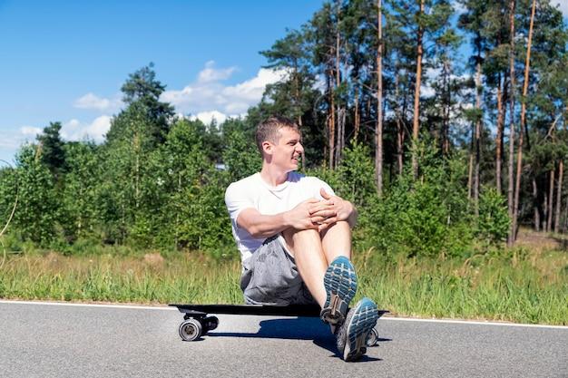 Junger erwachsener mann genießt das wetter, das auf einem skateboard vor dem hintergrund des waldes sitzt