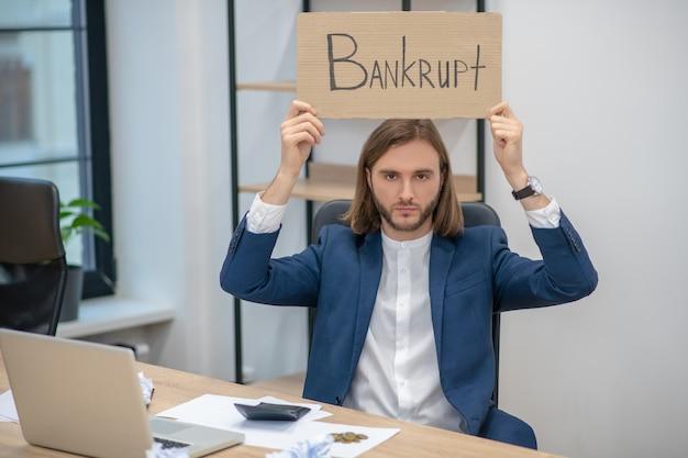 Junger erwachsener mann im geschäftsanzug mit erhöhtem bacrotplakat, das im büro sitzt