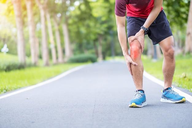 Junger erwachsener mann mit muskelschmerzen während des laufens