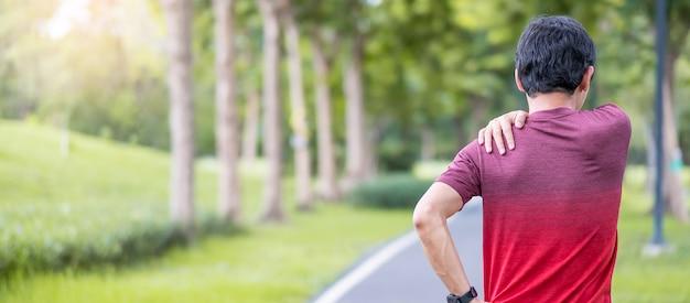 Junger erwachsener mann mit seinen muskelschmerzen während des laufens.