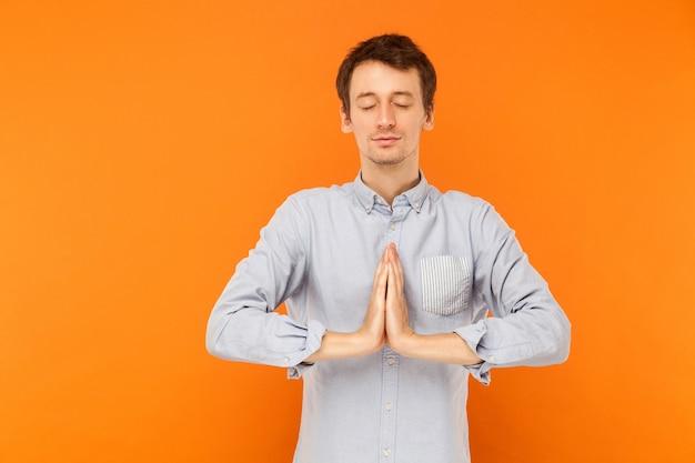 Junger erwachsener mann schloss die augen und betet