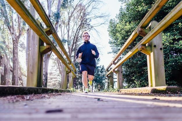 Junger erwachsener mann sportprofi, der im frühjahr oder sommer durch einen park läuft, trainiert am sonnenuntergangspunkt elitesport körperpflege tägliches training