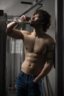 Junger erwachsener mann trinkt flasche wasser in der turnhalle