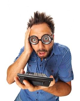 Junger erwachsener mit entsetztem ausdruck und taschenrechner