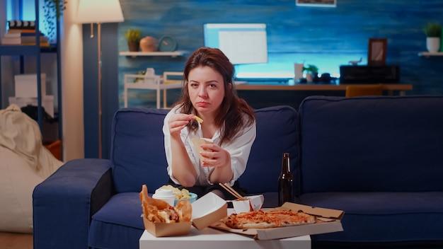 Junger erwachsener mit videoanruf-fernbedienung auf dem sofa sitzend