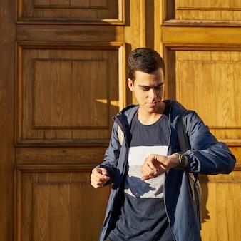 Junger erwachsener schaut auf die uhr. betonter kaukasischer mann mit dem schwarzen haar ängstlich, spät zu erhalten