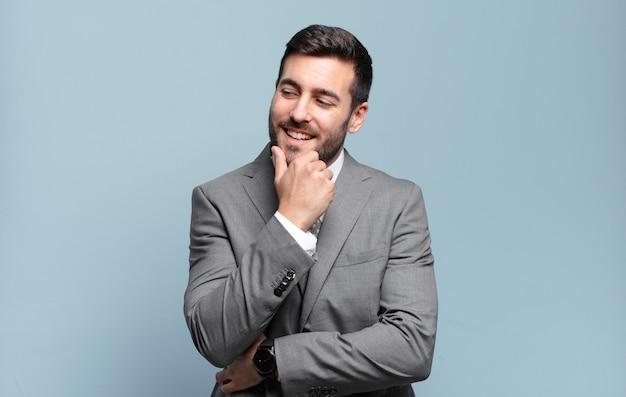 Junger erwachsener schöner geschäftsmann, der mit einem glücklichen, selbstbewussten ausdruck mit der hand am kinn lächelt, sich wundert und zur seite schaut