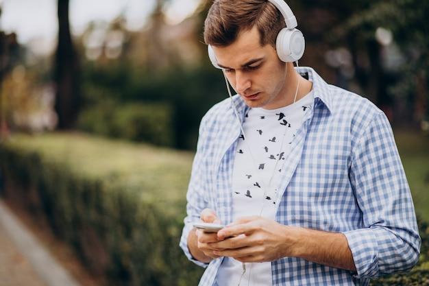 Junger erwachsener student, der die straße mit kopfhörern geht