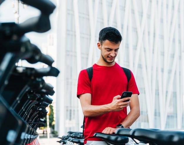 Junger erwachsener student, der mit seinem smartphone ein fahrrad mietet
